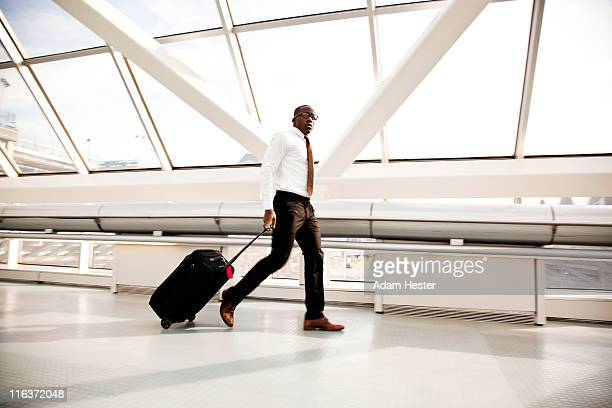 a businessman walking in an airport with luggage. - trousers stock pictures, royalty-free photos & images