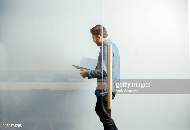 businessman walking in corridor reading notes - document stock pictures, royalty-free photos & images
