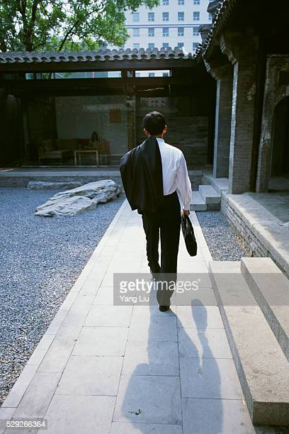 businessman walking in courtyard - liu he stock pictures, royalty-free photos & images