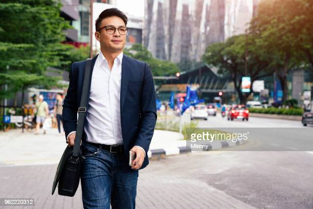 businessman walking in downtown kuala lumpur malaysia - young adult stock pictures, royalty-free photos & images