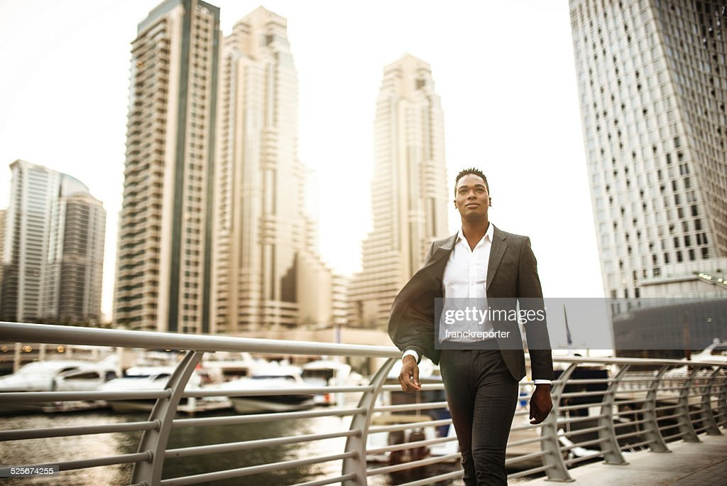 Businessman walking in dubai marina : Stockfoto