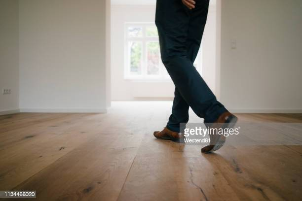 businessman walking in empty flat - floorboard stock photos and pictures