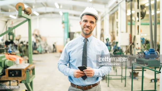 businessman walking in factory, looking at camera - sales occupation stock pictures, royalty-free photos & images