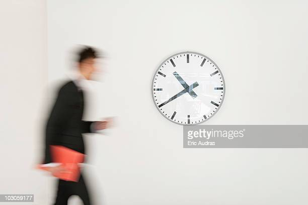 businessman walking in front of a clock - wall clock stock photos and pictures