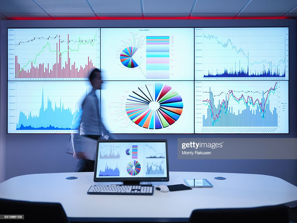 Businessman walking in front of graphs on screen : Stock Photo