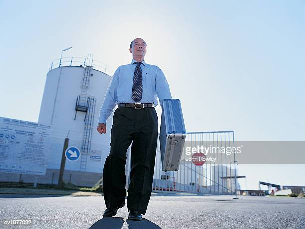 Businessman Walking in Front of the Gate to an Industrial Park