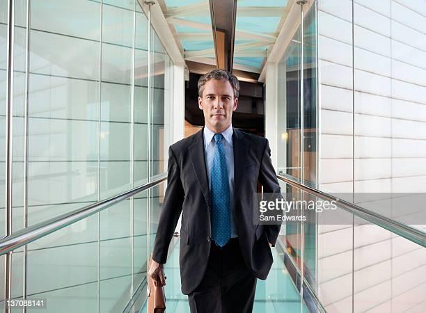 Geschäftsmann zu Fuß in Glas skyway