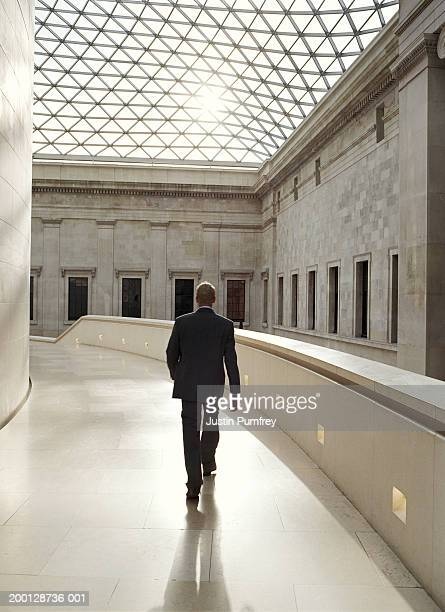 businessman walking in glass-roofed building - british museum stock pictures, royalty-free photos & images