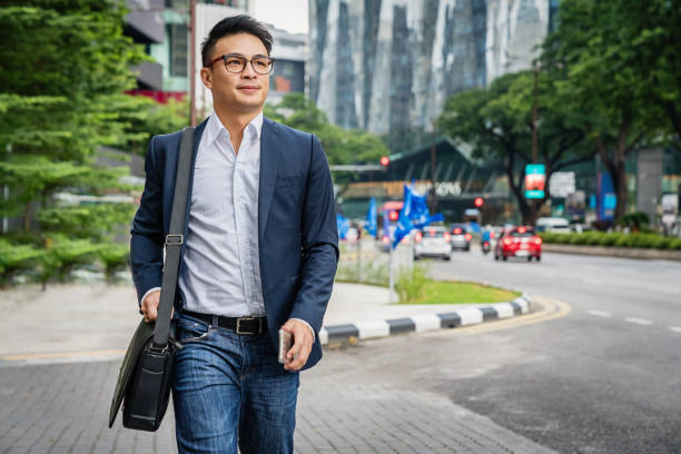 businessman walking in kuala lumpur malaysia - asian man walking on the streets stock pictures, royalty-free photos & images