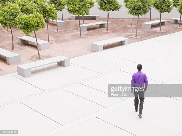 businessman walking in modern courtyard - purple shirt stock photos and pictures