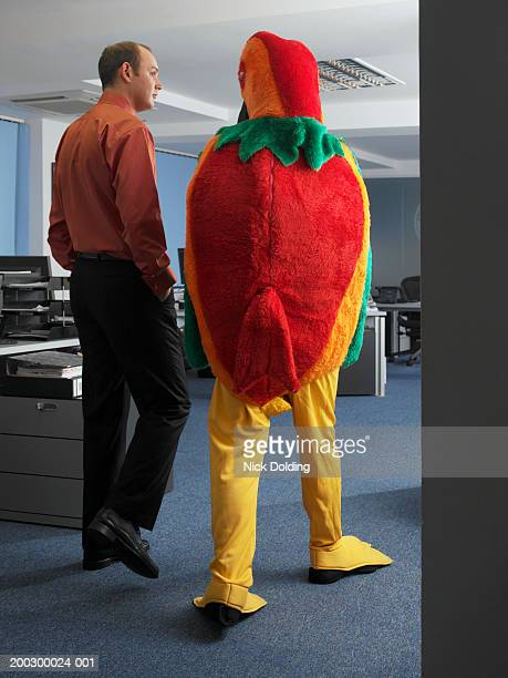 Businessman walking in office by man in bird costume
