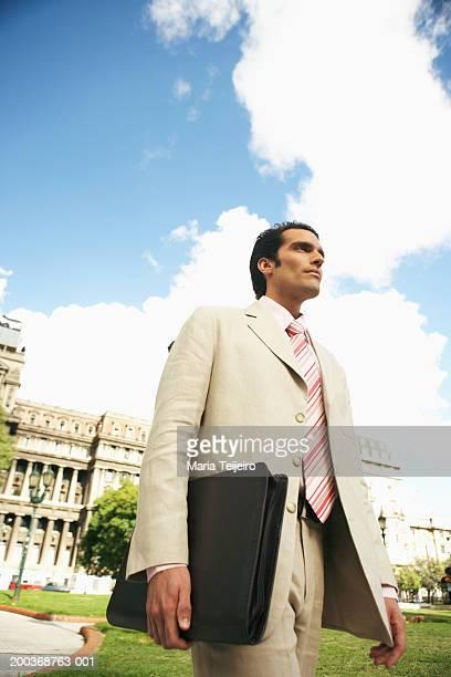 Geschäftsmann Aktentasche walking im park tragen, Flachwinkelansicht
