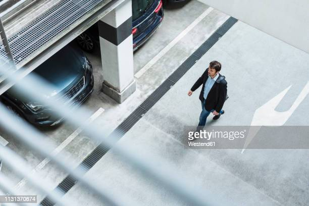 businessman walking in parking garage - parking garage stock pictures, royalty-free photos & images
