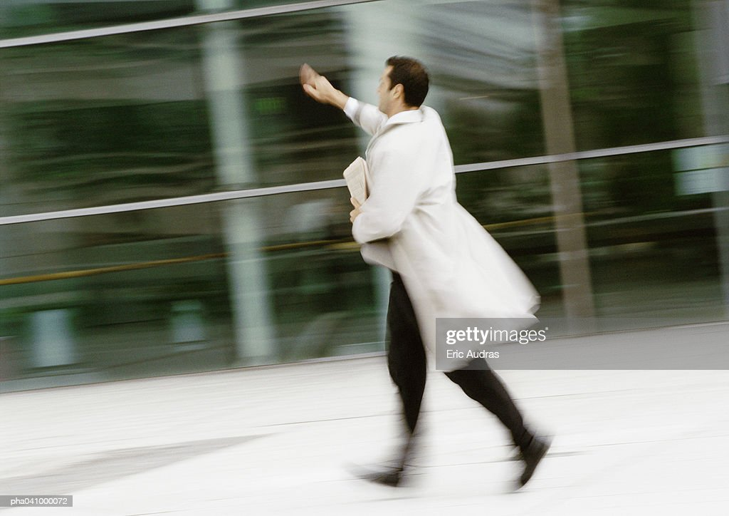 Businessman walking in street, hand raised, blurred : Stock Photo