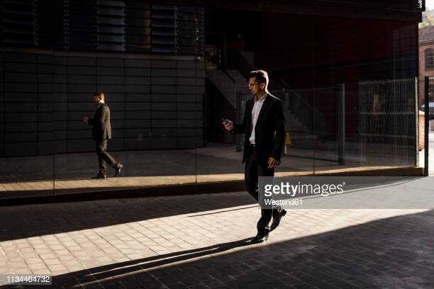 businessman walking in the city checking cell phone - elegantie stockfoto's en -beelden