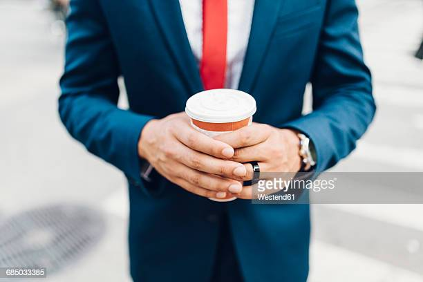 Businessman walking in the city, holding cup of coffee
