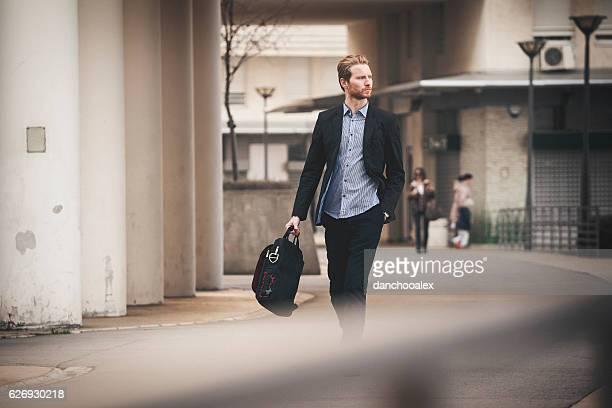 homme d'affaires marchant dans la ville - sac à main blanc photos et images de collection