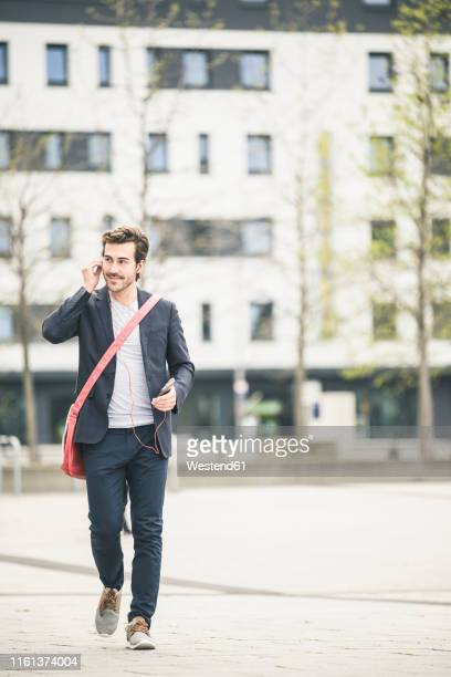 businessman walking in the city with cell phone and earphones - inserting stock pictures, royalty-free photos & images