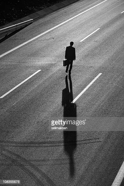 Businessman walking in the middle of highway, shadow on road