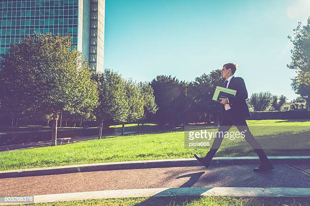 Businessman walking in the park of a city