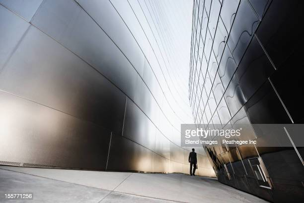 businessman walking in urban alley - arquitetura imagens e fotografias de stock