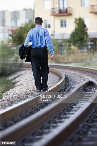 Businessman Walking Next to Railroad Tracks