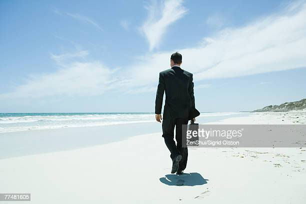 Businessman walking on beach, carrying briefcase