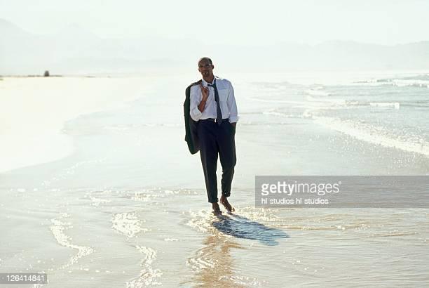 Businessman walking on beach