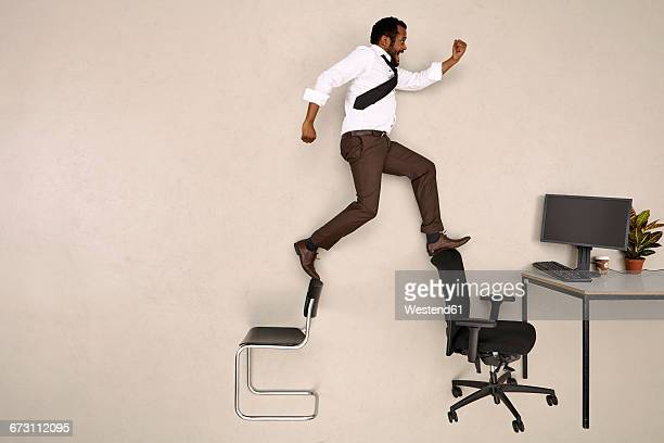 Businessman walking on chairs towards office desk