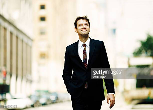 Businessman walking on city street, looking upward