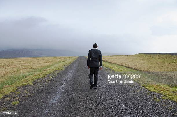 Businessman walking on deserted gravel road