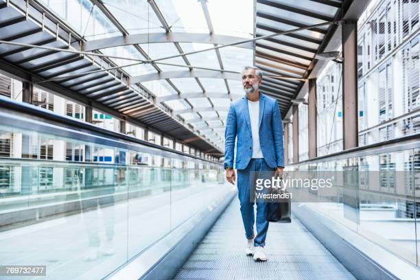 businessman walking on moving walkway - looking in bag stock pictures, royalty-free photos & images