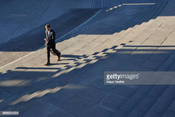 Businessman walking on outside staircase and looking at phone