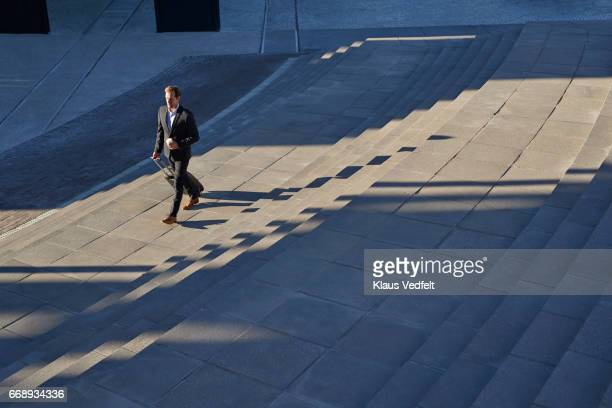 Businessman walking on outside staircase with suitcase