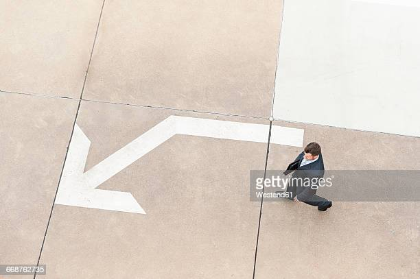 Businessman walking on paving with large arrow