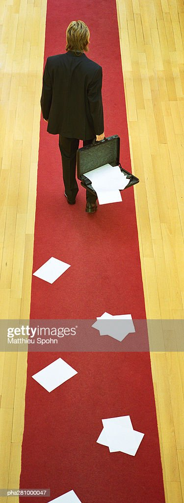 Businessman walking on red carpet, holding open briefcase, papers falling out of briefcase : Stockfoto