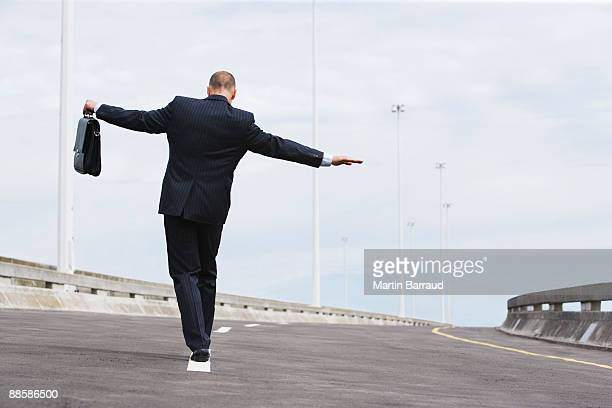 Businessman walking on road lane divider