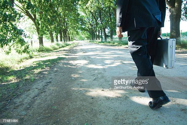 Businessman walking on rural road, low section