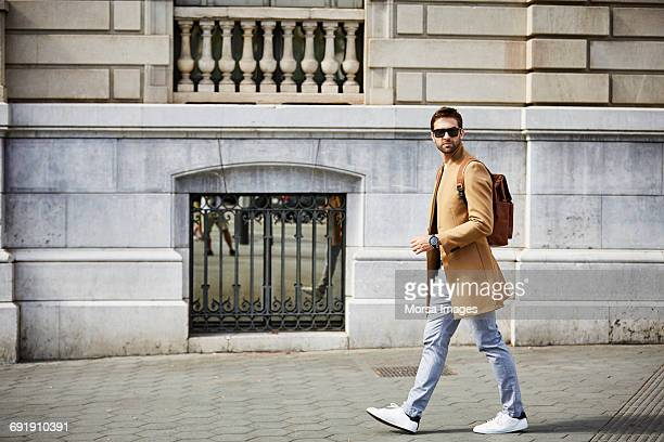 Businessman walking on sidewalk by building