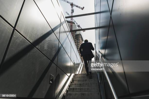 businessman walking on staircase in the city - steps and staircases stock pictures, royalty-free photos & images