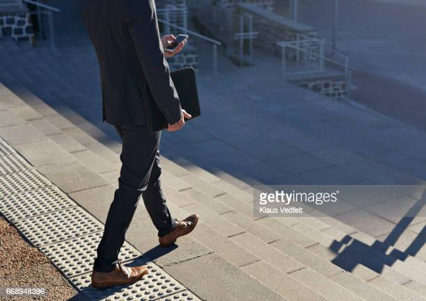 Businessman walking on staircase with phone