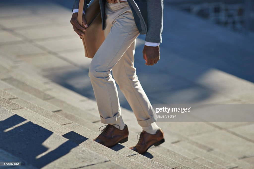Businessman walking on staircase with shoulder bag : Stock Photo