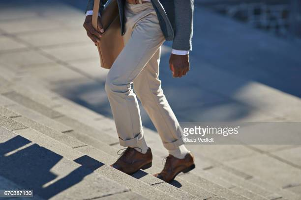 Businessman walking on staircase with shoulder bag