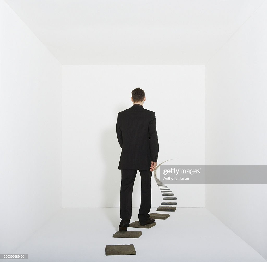 Businessman walking on stepping stones in white room, rear view : Stock Photo