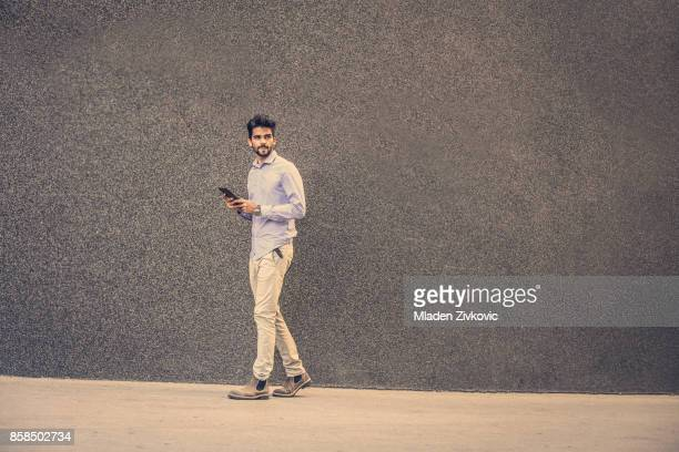 businessman walking on street and using ipod. space for copy. - one young man only stock pictures, royalty-free photos & images