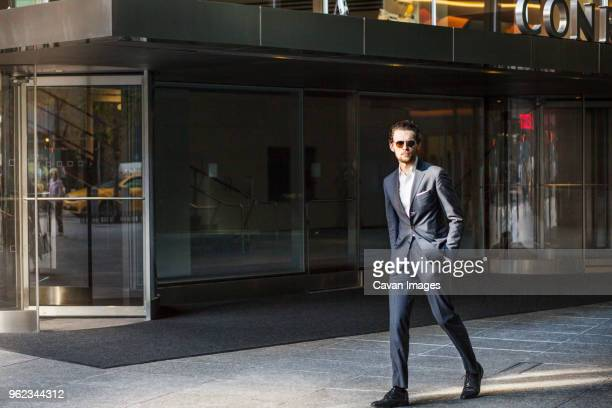 businessman walking on street by in city against clear sky - formal stock pictures, royalty-free photos & images