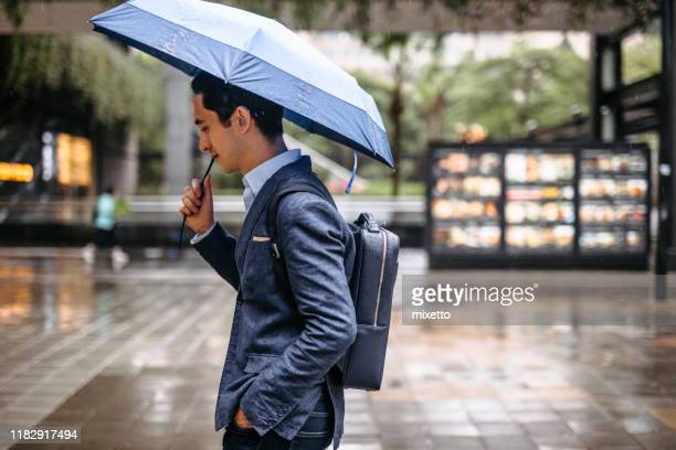 businessman walking on street with umbrella - torrential rain stock pictures, royalty-free photos & images