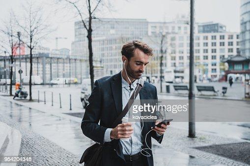 Unternehmer, die auf der Straße Musik hören und mit Smartphone