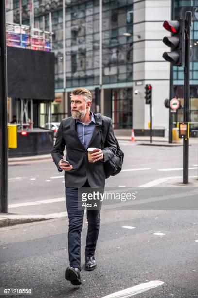 hombre de negocios caminando por la calle - cruzar fotografías e imágenes de stock
