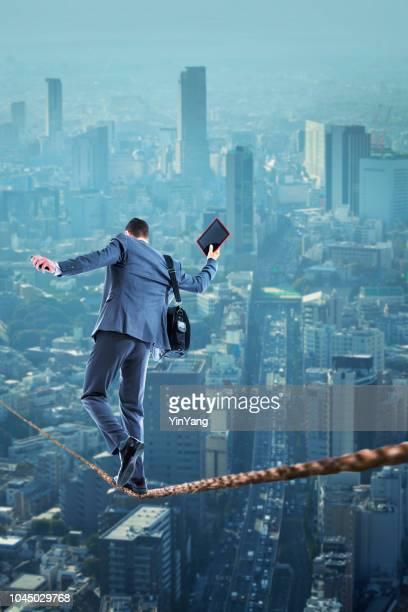 タイトロープの上を歩くビジネスマン街上空 - 綱渡りのロープ ストックフォトと画像